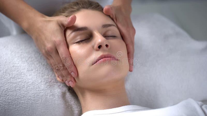 Pele hidratando dos clientes do Cosmetologist, fazendo massagens a pele da cara, efeito da anti-idade fotografia de stock