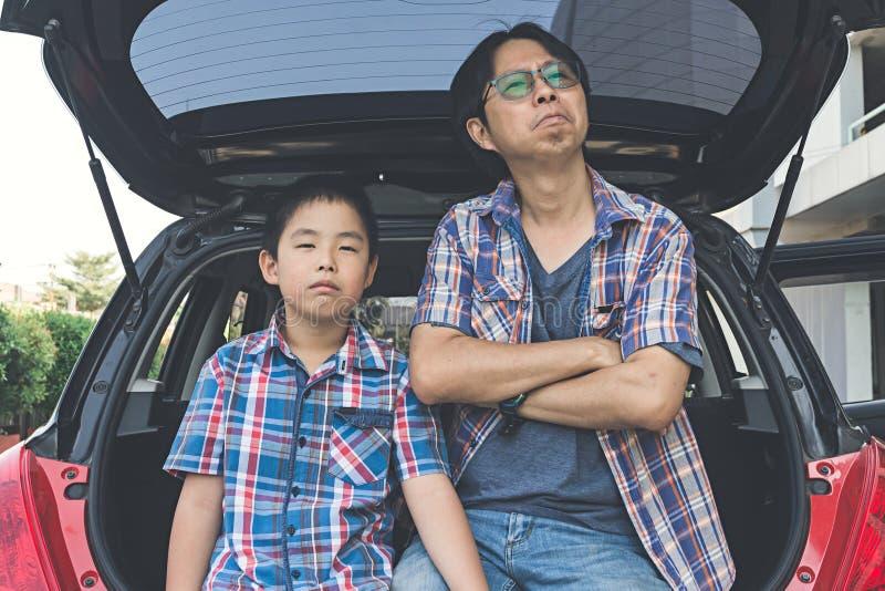 Pelea del pequeño hijo y del padre que se sientan en el tronco del coche fotografía de archivo libre de regalías