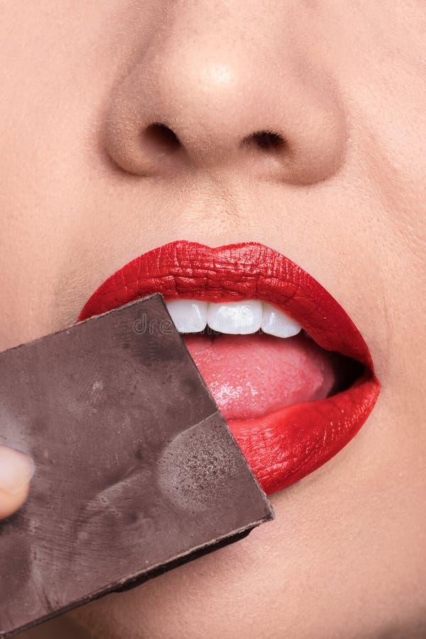 Pelez le plan rapproché de lèvres léchant le chocolat, rouge à lèvres rouge images stock