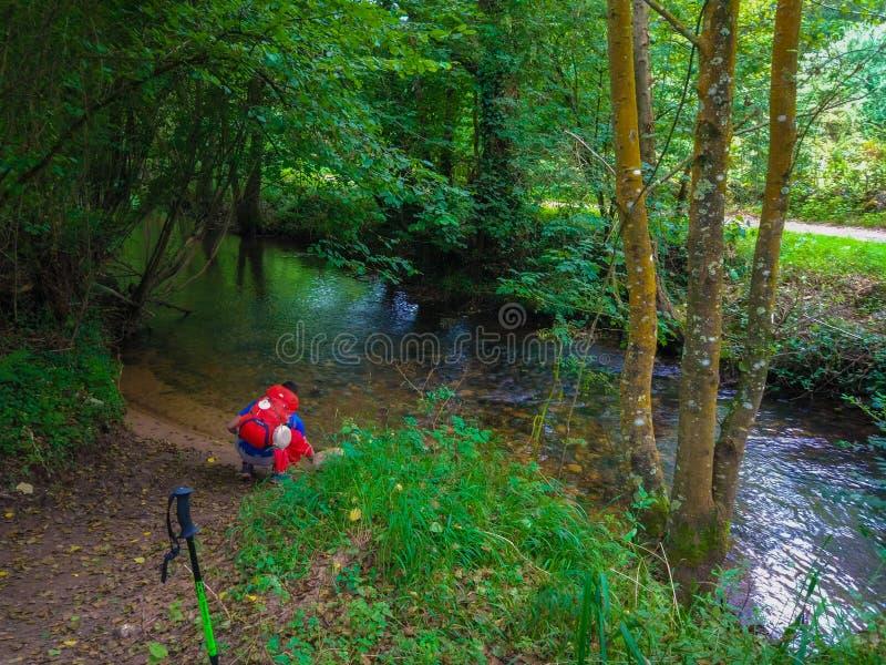 Pelgrim of backpacker drinkwater van een rivier in midden van t royalty-vrije stock afbeelding