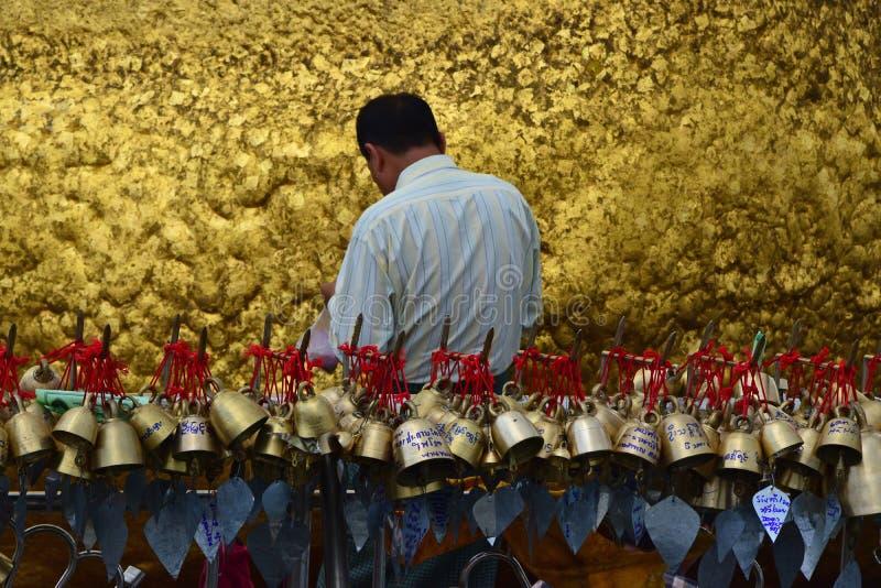 Pelgrim die gouden folies op gouden rots bij de Kyaiktiyo-Pagode, Myanmar met rij van kleine klokken in voorgrond kleven stock fotografie