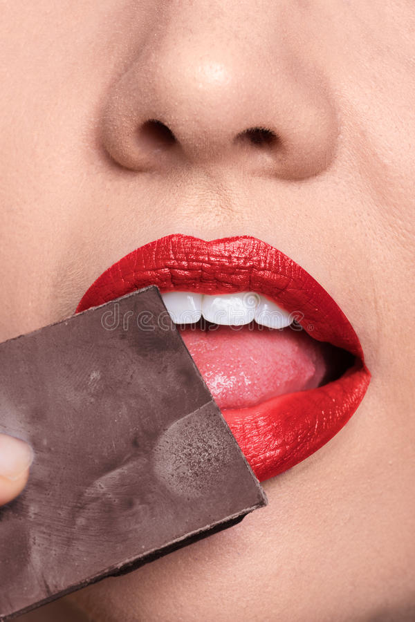 Peli il primo piano delle labbra che lecca il cioccolato, rossetto rosso immagini stock