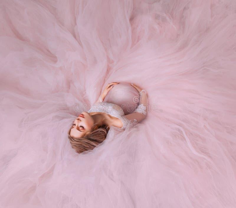 Peli incinti innocenti attraenti meravigliosi della ragazza sul pavimento nel nero di un vestito splendido rosa elegante costoso immagini stock libere da diritti