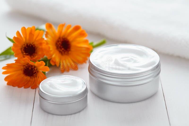 Peli la crema cosmetica struccante con la lozione della stazione termale della vitamina dei fiori della calendula fotografia stock