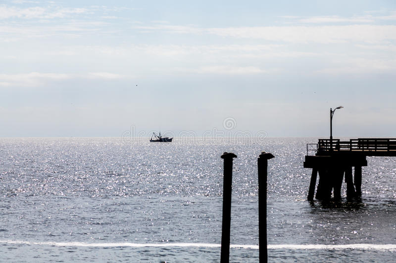 Pelicans Pier and Shrimp Boat silhouette royalty free stock photography
