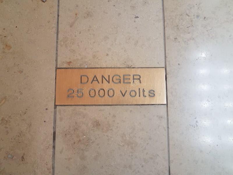 Peligro 25000 voltios de señal de peligro en suelo de baldosas foto de archivo libre de regalías