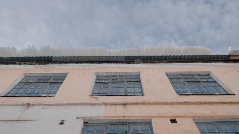 Peligrosa cornisa de nieve en el borde del techo fotografía de archivo
