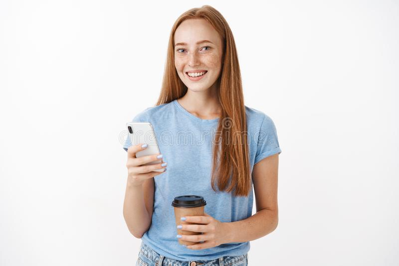 Pelirrojo femenino lindo, feliz con las pecas que sonríe en la cámara que pide consejo del amigo cómo acto durante mandar un SMS  imágenes de archivo libres de regalías