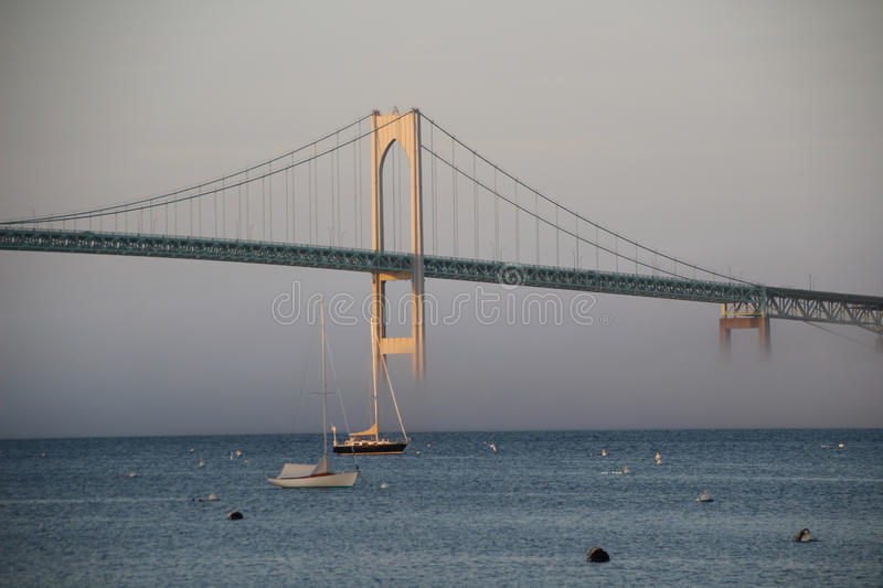 Pell Bridge in Newport RI in fog. The beautiful Pell Bridge from Jamestown, RI to Newport RI USA in fog with a sailboat in foreground royalty free stock photo