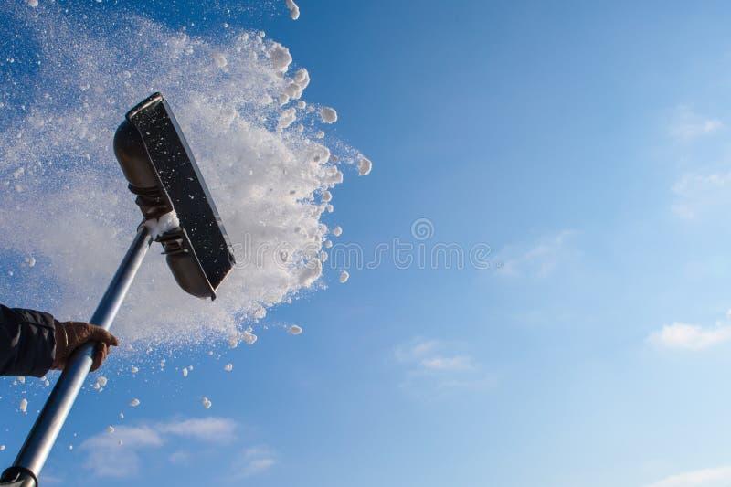 Pelle à neige de nettoyage, neige de lancement images libres de droits
