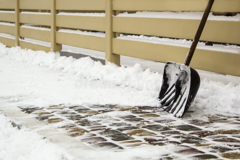 Pelle à neige près de barrière sur une route neigeuse photographie stock libre de droits