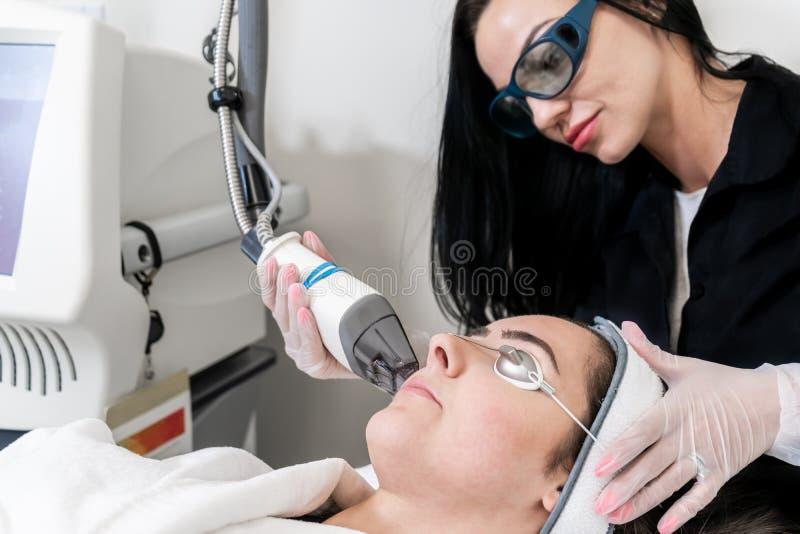 Pelle d'esecuzione del tecnico del laser di bellezza che rifa la superficie della procedura in una clinica medica di bellezza e d fotografie stock