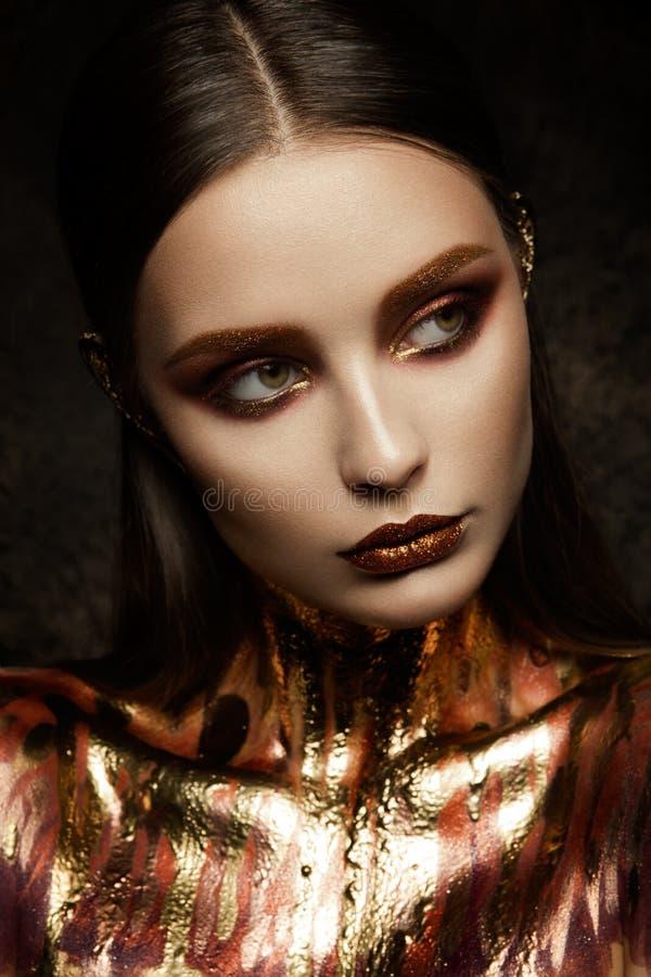 Pelle della donna dell'oro immagine stock