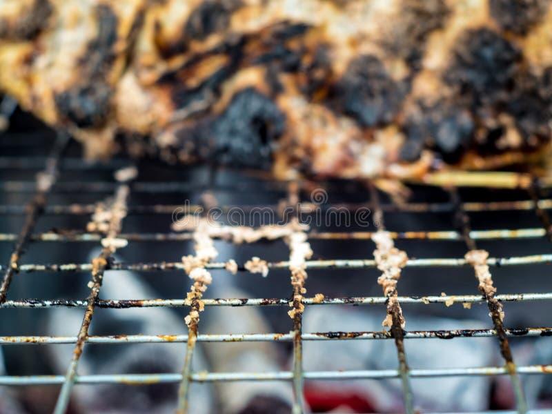 Pelle della griglia del pesce su carbone caldo fino a nero e bruciacchiato immagine stock libera da diritti