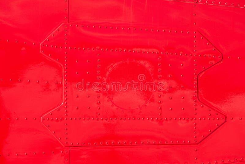 Pelle di fusoliera rivettata dipinta rosso dell'aeroplano del metallo fotografie stock libere da diritti