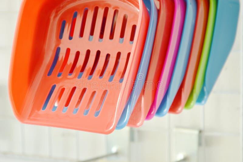 Pelle en plastique colorée à litière du chat accrochant sur des affichages de crochet dans le magasin de bêtes photographie stock libre de droits