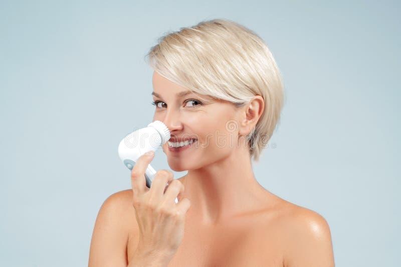 Pelle felice del fronte di pulizia della donna con la spazzola Bellezza e stazione termale immagine stock libera da diritti