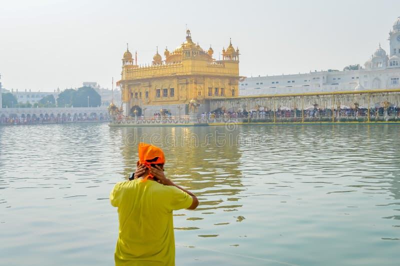 Pellegrino sikh che prega in carro armato santo vicino al tempio dorato Sri Harmandir Sahib, Amritsar, INDIA immagini stock