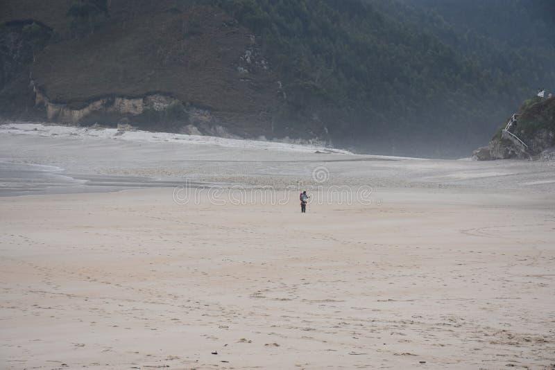 Pellegrino solo su una spiaggia in Asturie sul Camino de Santiago fotografia stock libera da diritti