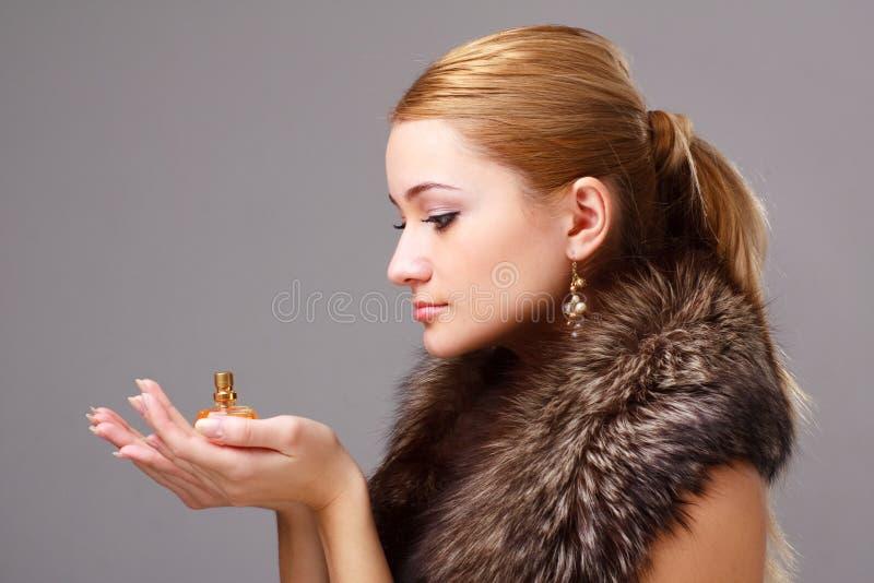 Pelliccia da portare della giovane donna con profumo fotografie stock libere da diritti