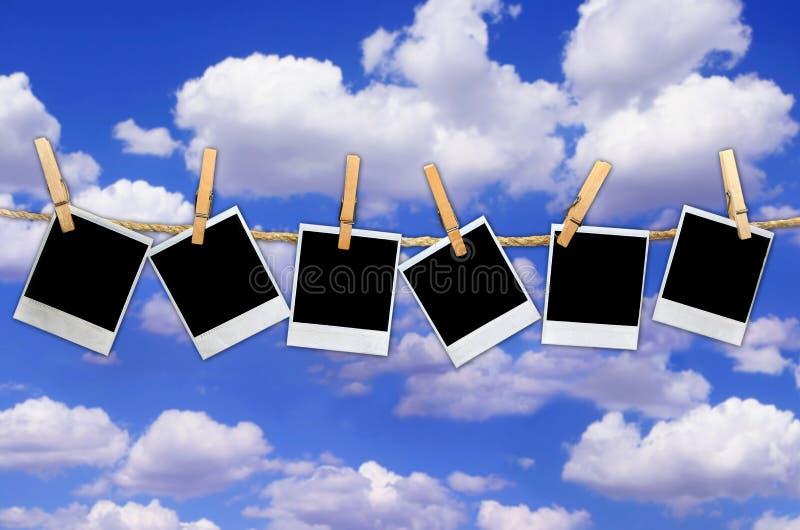 Pellicole del Polaroid che appendono sui cenni storici del cielo fotografia stock