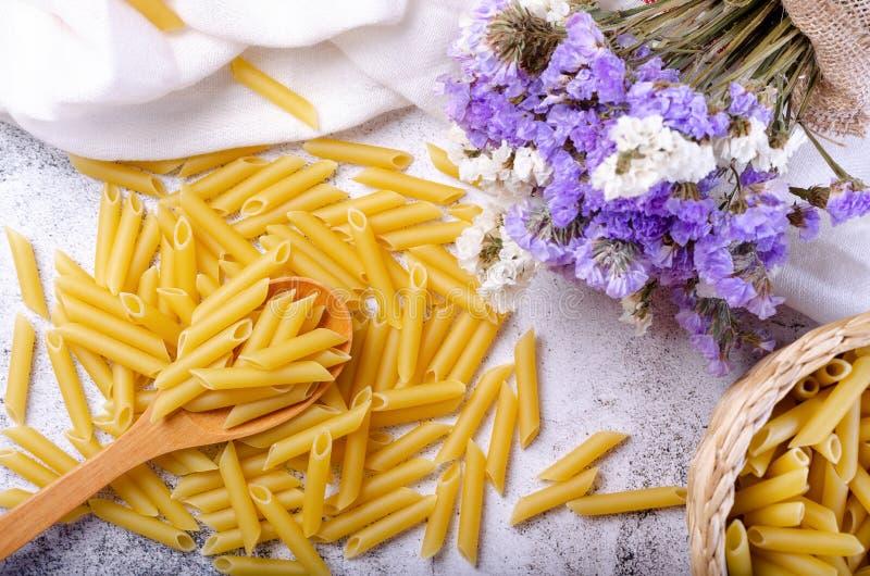 Pellicole di farina di pasta e di penne su cucchiai di legno immagini stock libere da diritti