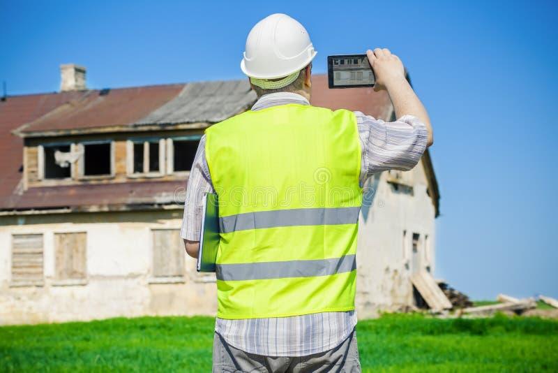 Pelliculage d'inspecteur des bâtiments sur la tablette près de la vieille maison abandonnée et endommagée sur le champ d'herbe photos stock