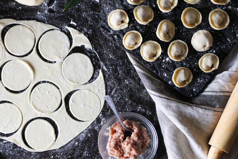 pelmeni的准备 顶视图 在黑桌上的成份 烹调俄国传统 免版税库存图片