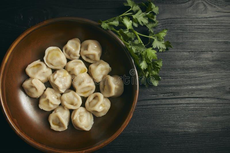 Pelmeni con burro e verdi su una tavola di legno nera Piatto tradizionale russo di pasta e di carne tritata Chiuda sulla foto fotografie stock