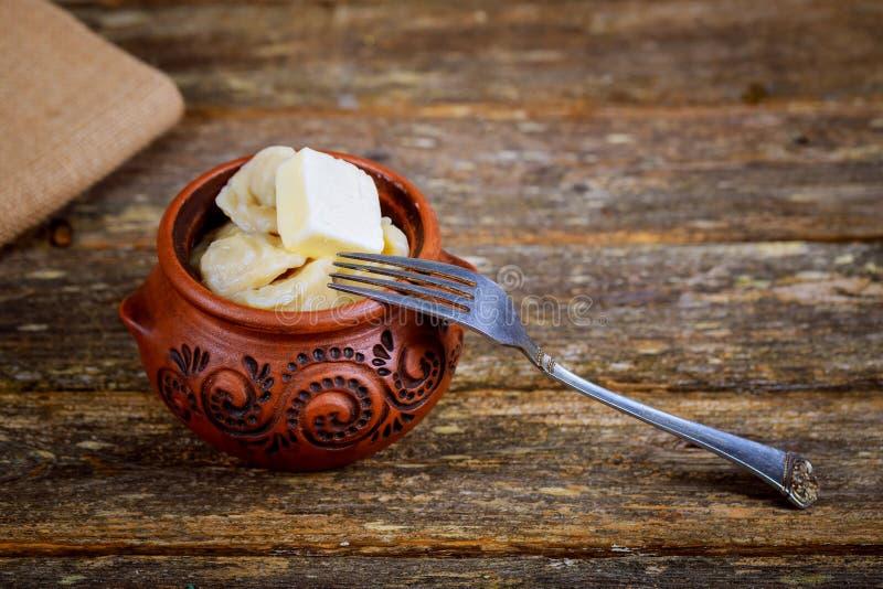 Pelmeni de boulettes de viande avec la crème sure sur le fond rustique image stock