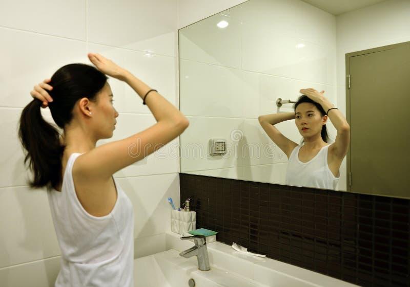Pelo de cepillado de la mujer asiática delante del espejo en cuarto de baño foto de archivo