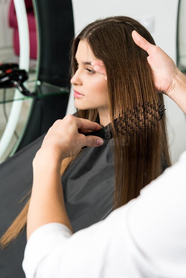 Pelo de cepillado del peluquero de la mujer foto de archivo libre de regalías