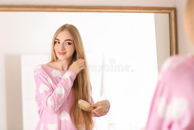 Pelo de cepillado de la mujer joven en cuarto de baño foto de archivo