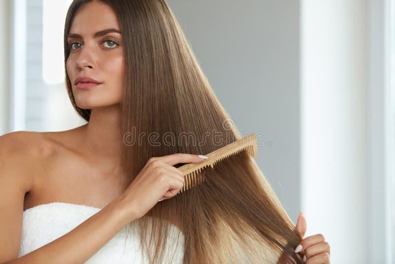 Pelo de cepillado Pelo largo hermoso de Hairbrushing de la mujer con el peine foto de archivo