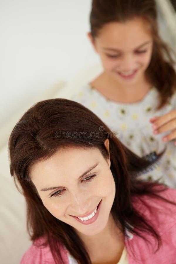 Pelo de la madre que aplica con brocha de la chica joven fotografía de archivo libre de regalías