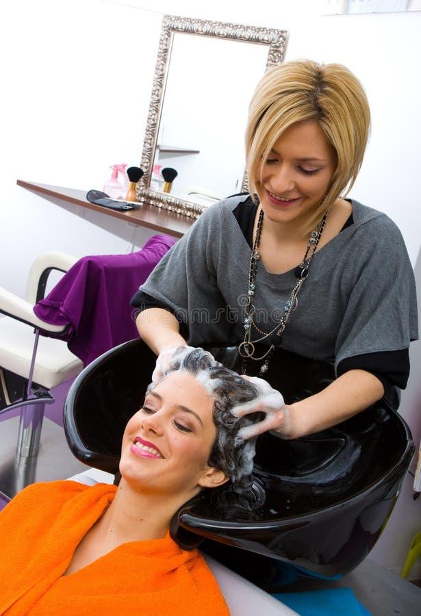 Pelo de la mujer del estilista de pelo que se lava foto de archivo libre de regalías