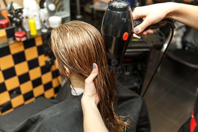 Pelo de teñido del peluquero profesional de su cliente en salón Cabello seco del peluquero con más hairdrier Foco selectivo fotos de archivo