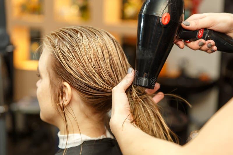 Pelo de teñido del peluquero profesional de su cliente en salón Cabello seco del peluquero con más hairdrier Foco selectivo fotos de archivo libres de regalías