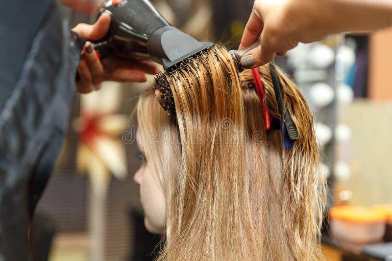 Pelo de teñido del peluquero profesional de su cliente en salón Cabello seco del peluquero con más hairdrier Foco selectivo imagen de archivo libre de regalías
