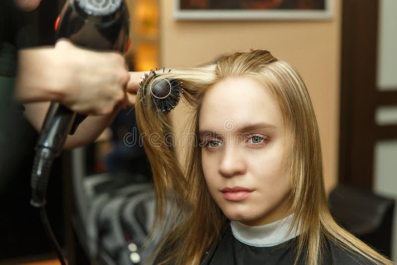 Pelo de teñido del peluquero profesional de su cliente en salón Cabello seco del peluquero con más hairdrier Foco selectivo foto de archivo libre de regalías