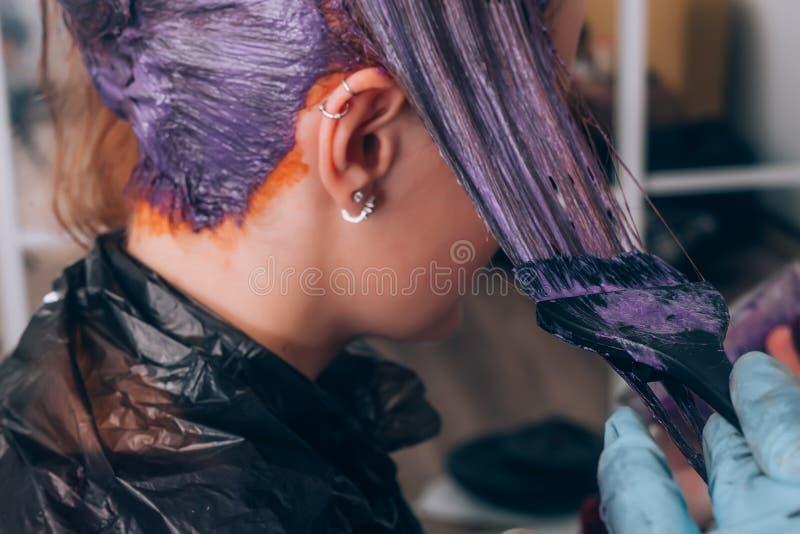 Pelo de teñido del peluquero profesional de su cliente en salón Foco selectivo foto de archivo libre de regalías