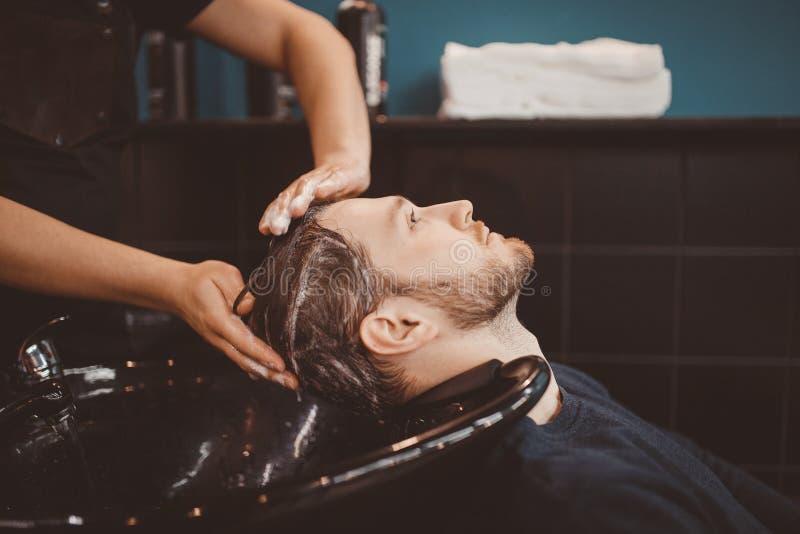 Pelo del cliente del lavado del peluquero en peluquería de caballeros fotos de archivo
