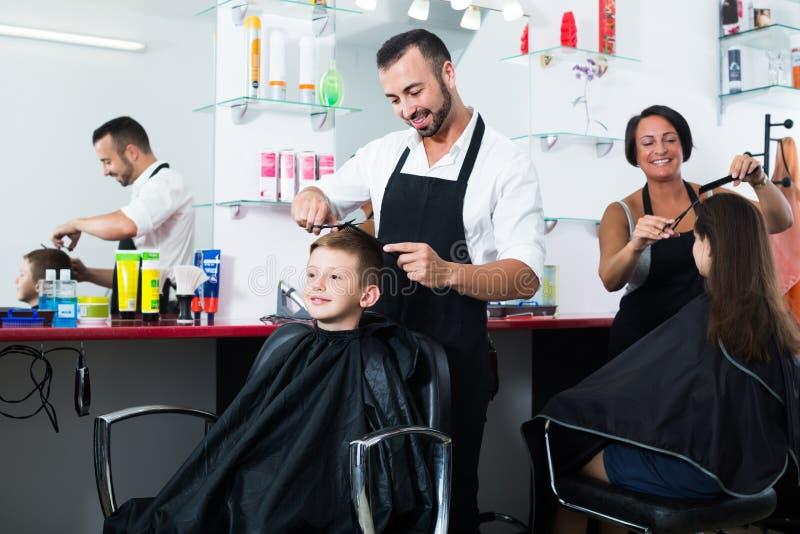 Pelo del corte del peluquero del muchacho en salón fotos de archivo libres de regalías
