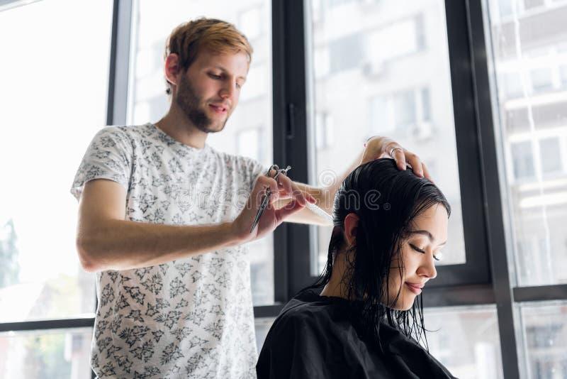 Pelo del ` s del cliente del corte del peluquero en salón con el primer de las tijeras Usando un peine fotos de archivo