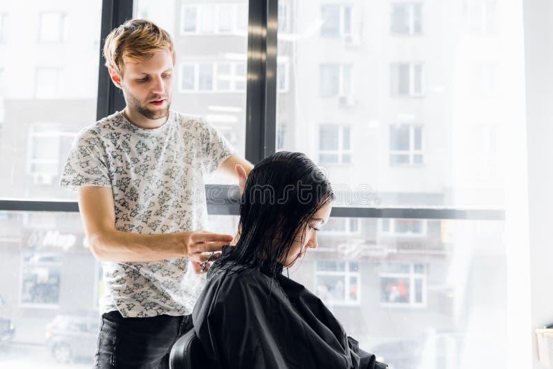 Pelo del ` s del cliente del corte del peluquero en salón con el primer de las tijeras Usando un peine imágenes de archivo libres de regalías