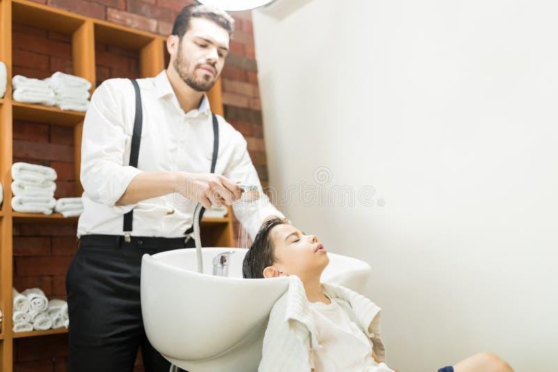 Pelo del ` s de Washing Client del peluquero en fregadero en Barber Shop foto de archivo libre de regalías
