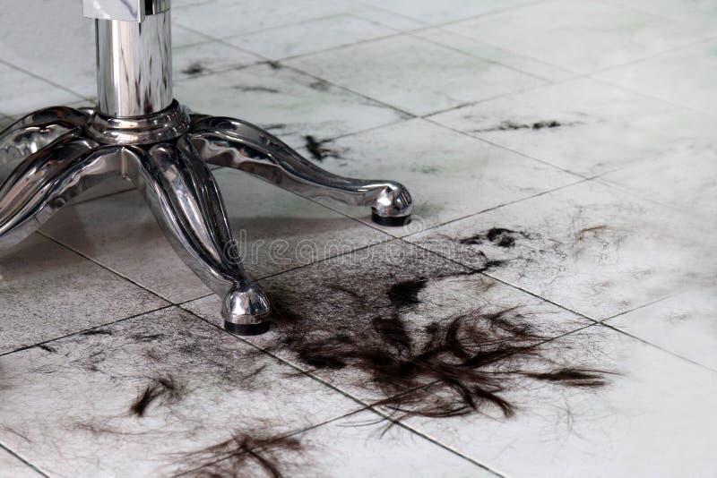 Pelo en el piso en la peluquería de caballeros, peluqueros, pedazo del pelo del recortes del corte de pelo, pila de pelo sucia fotografía de archivo libre de regalías