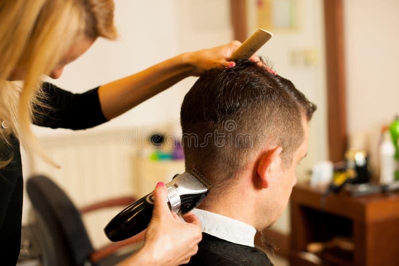 Pelo femenino del corte del peluquero del cliente sonriente del hombre en la belleza fotos de archivo