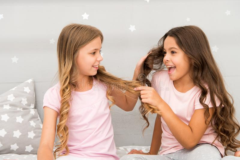 Pelo fuerte Juego alegre de los niños con el pelo en dormitorio Momentos felices de la niñez Embroma a mejores amigos de las herm fotografía de archivo
