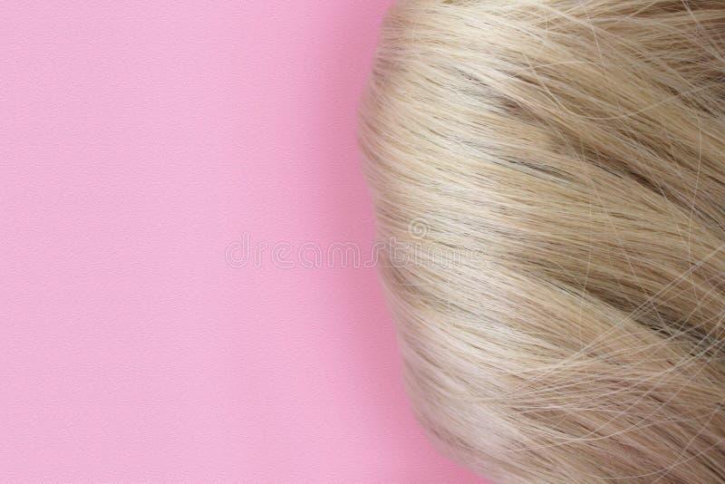 Pelo hermoso Pelo marr?n claro El pelo se recolecta en un bollo en un fondo rosado con el espacio libre para el texto Para un car fotografía de archivo libre de regalías